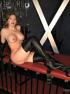Femdom Goddess is posing in all her beauty: naked on top of the BDSM cage and wearing a pair of leather knee-boots