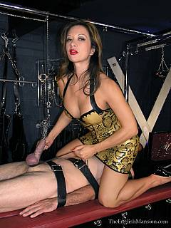Classy babe in latex is applying electricity to the card cock while male slave himself is strapped helplessly to the table