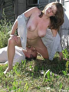 Husband is lying in the grass while slutty wife is sitting on his face with her nyloned ass