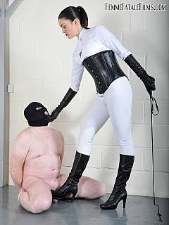 Gorgeous dominatrix is dressed up in white, wearing corset and holding riding crop in her hands to control slave with