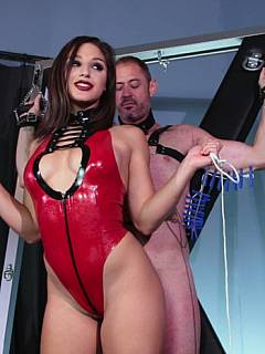 Helplessly exposed on the BDSM cross and taking abuse from the sexy young lady in red latex