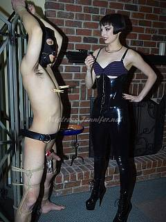 Hot babe in rubber is taking naked male to the limit with BDSm rack bondage, CBT and degrading strap-on sex
