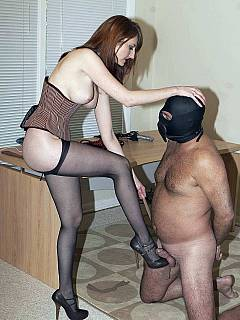 Erotic mistress is using pantyhose to tie her slave down getting ready to bust his balls