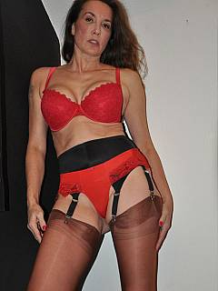 Black leather, red lingerie and seamed stockings is the classic outfit for the sexy dominatrix
