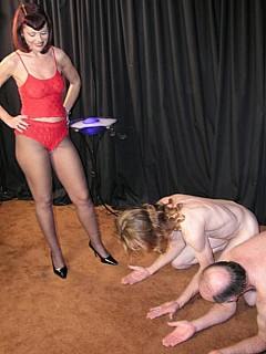 Two naked submissive are walked over by a girl in heels and black pantyhose
