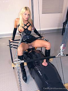 Male slave is bound with tape and suspended as a sort of love swing sexy dominatrix is riding