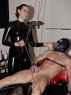 Hot domme in glossy black rubber is giving slave hard times tormenting his manhood in series of BDSM tortures