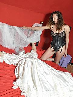 Cruel bitch with rubber strap-on cock attached is having sissy spread-eagled in bed and ready for mouth fucking