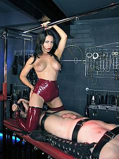 Hot domme in latex panties is busy teasing cock and denying orgasms while male slave is bound with belts
