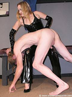 Girl is wearing glossy rubber costume to make femdom spanking scene more enjoyable