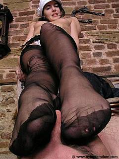 Femdom session where male sub is sniffing nude girl's feet under thin layer of nylon