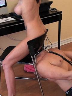 Masked slave becomes a part of the chair erotic MILF Goddess is siting on while surfing Internet