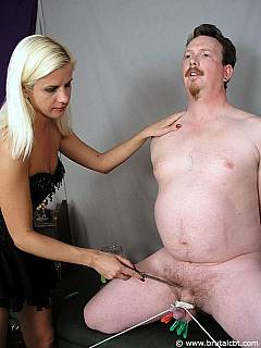 Kneeling dude has his small cock tied up, clamped and there is a sharp knife blond holding in her hands getting ready for castration