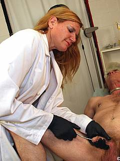 Older redhead is penetrating penis with steel rod putting exposed man in extreme pain