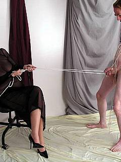 Mature mistress is controlling her slave by pulling the rope tied to his balls