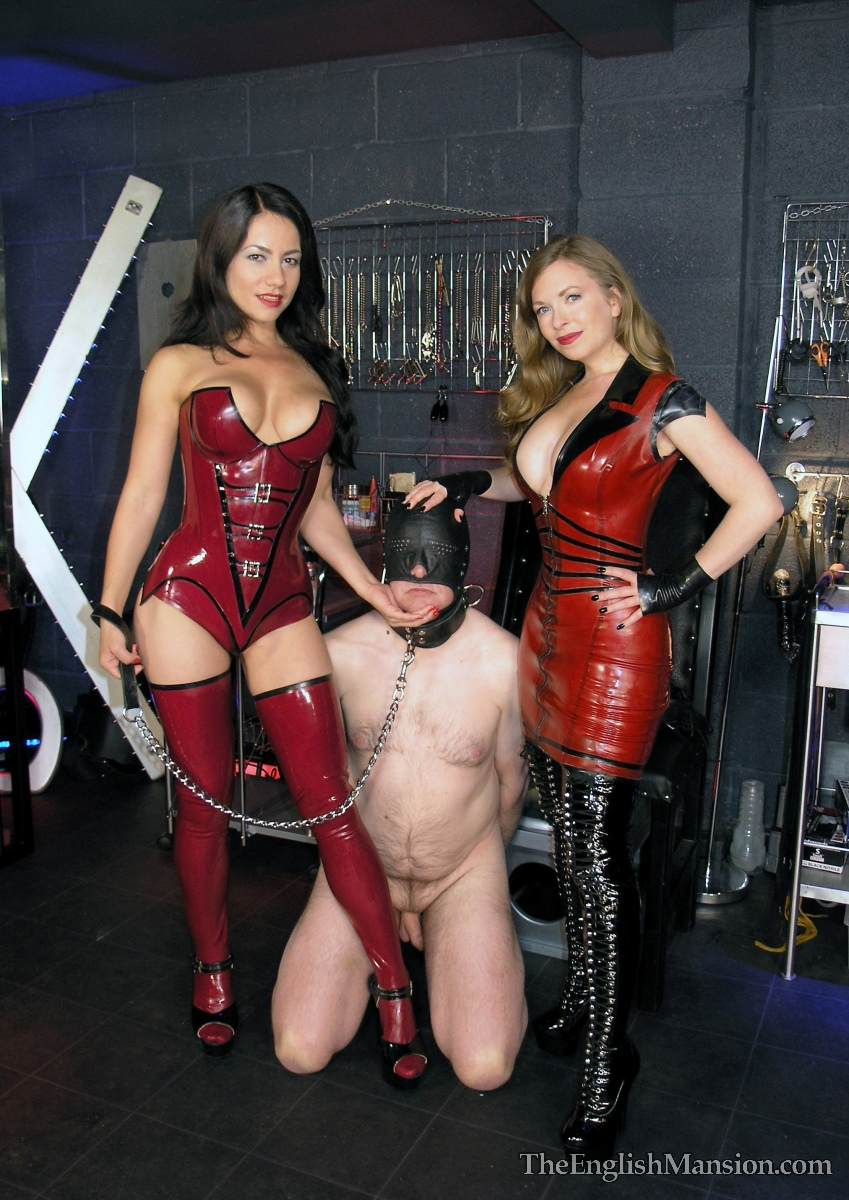 Picture #2 of Hot girls in latex are joinint their efforts to teach a couple of femdom slaves to suck each other dicks