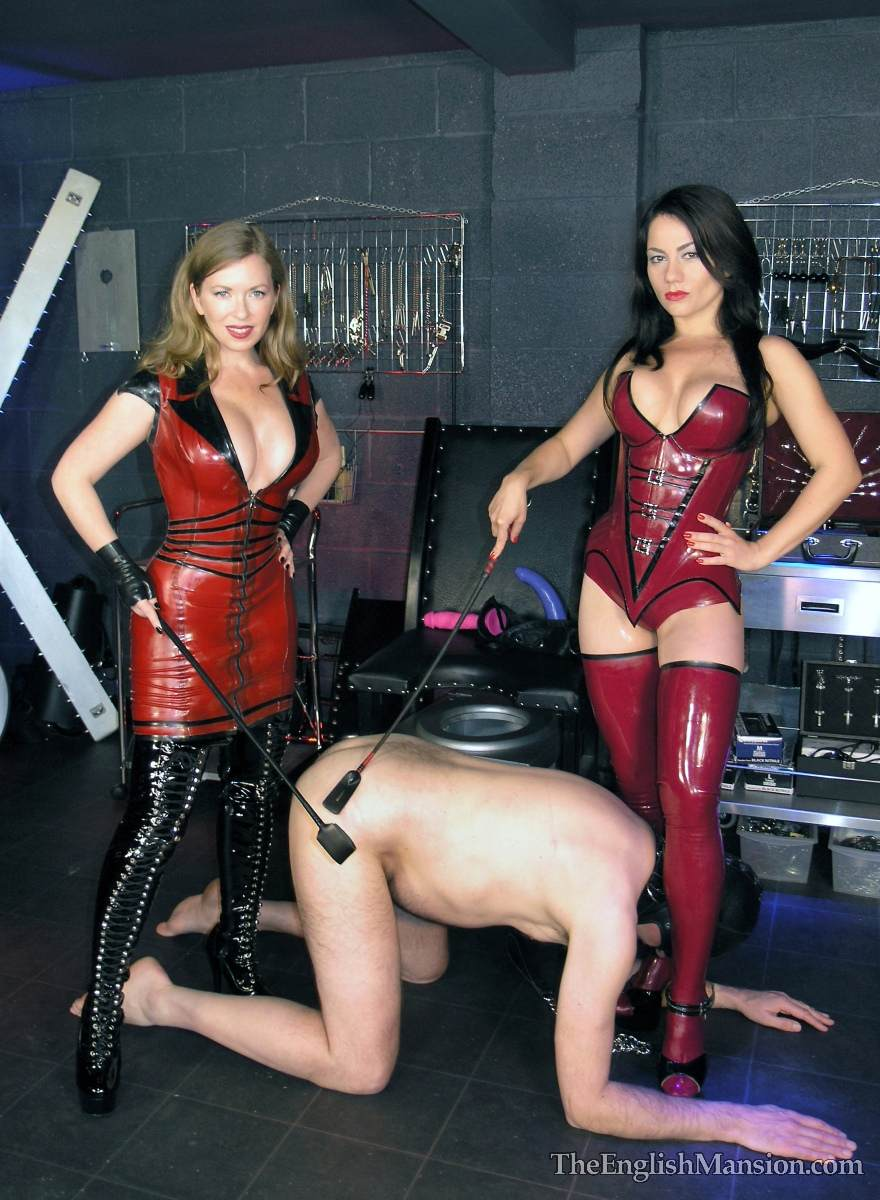 Picture #5 of Hot girls in latex are joinint their efforts to teach a couple of femdom slaves to suck each other dicks