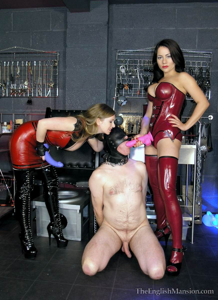 Picture #7 of Hot girls in latex are joinint their efforts to teach a couple of femdom slaves to suck each other dicks