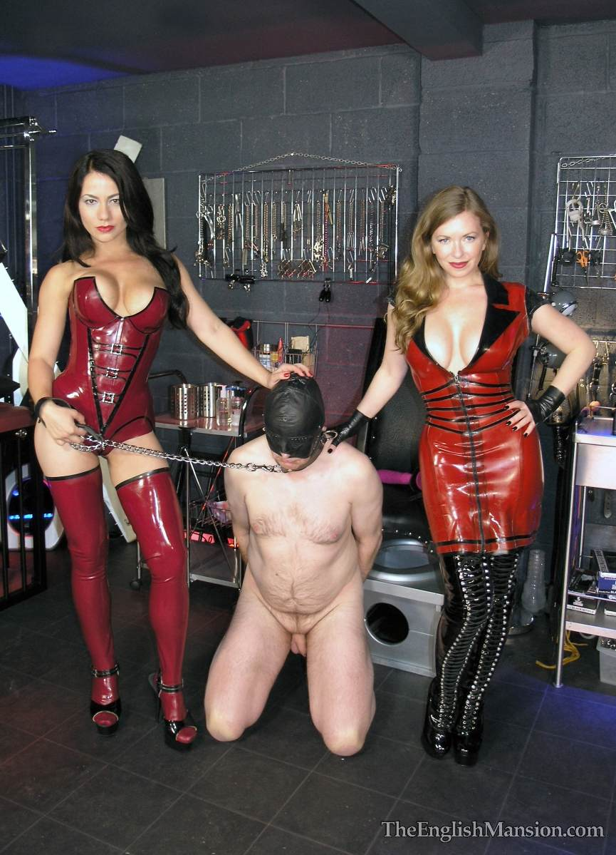 Picture #19 of Hot girls in latex are joinint their efforts to teach a couple of femdom slaves to suck each other dicks