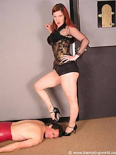 Redhead woman is using her legs to put man into submission and trampling him afterwards in high heels