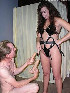 MILF in fetish harness is stretching yet another ass with sex toy, celebrating female superiority over men