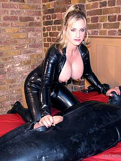 Busty lady in black cat-suit put male into rubber bag lesbian his cock outside to play with and to tease