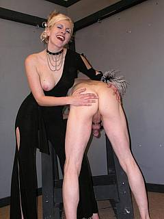 Dominatrix in posh dress is spanking kneeling an so hard that one of her boobs jumps out of the clothing