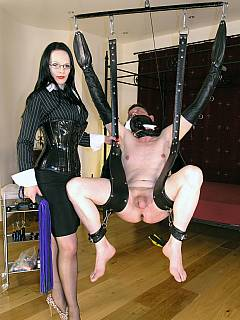 Naked man is placed into leather BDSM gear and suspended up in the air for series of tortures by sexy strict lady