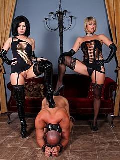 A team of two sexy dommes are both wearing kinky slutty mini mini-dresses when using wooden BDSM rack for femdom slave training