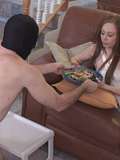 Nicely-trained slave is delivering lunch to his mistress and kissing her bare feel while she is enjoying her meal
