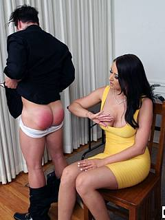 Busty babe with sexy cleavage is using paddle on the man over her knees and then spanks him hard