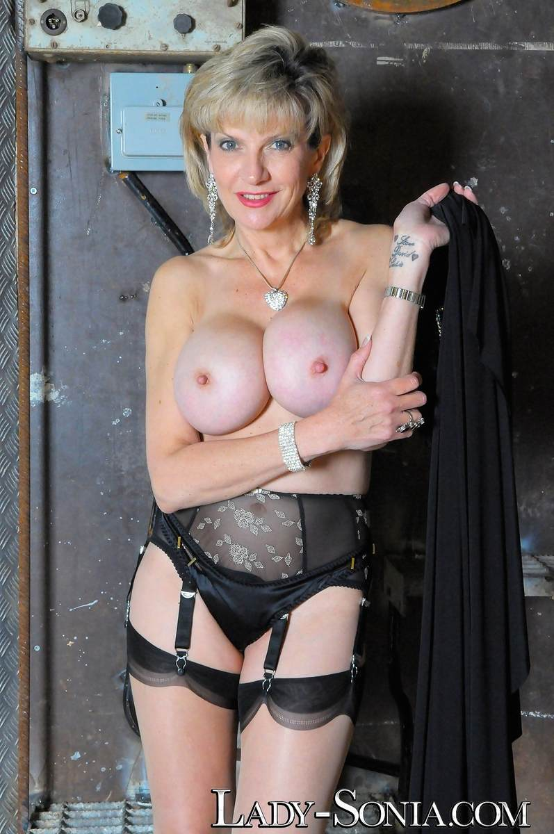 Picture #1 of Stockings and garter belt is the only clothing busty dominatrix will be wearing when taking cage of you and your penis