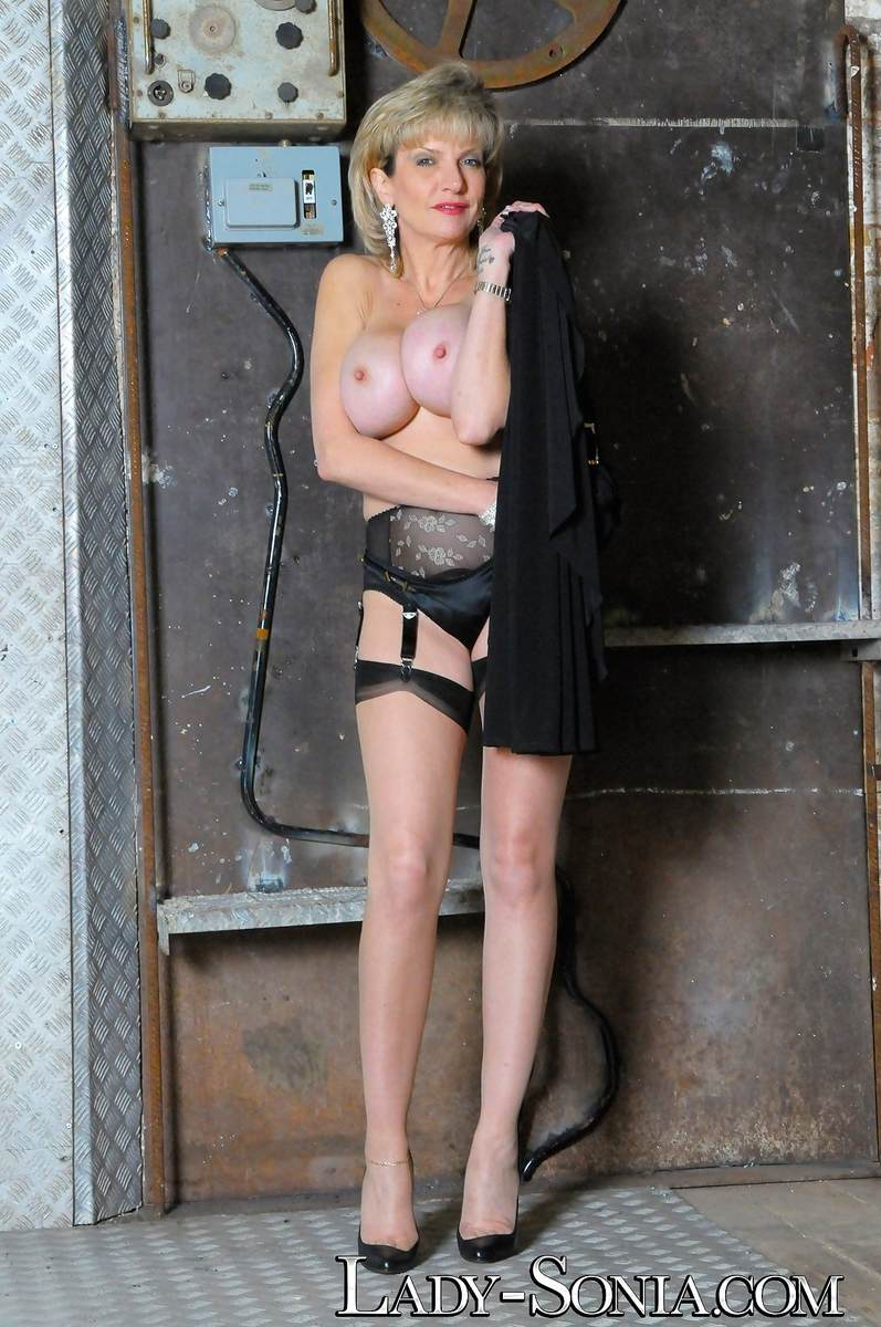 Picture #2 of Stockings and garter belt is the only clothing busty dominatrix will be wearing when taking cage of you and your penis