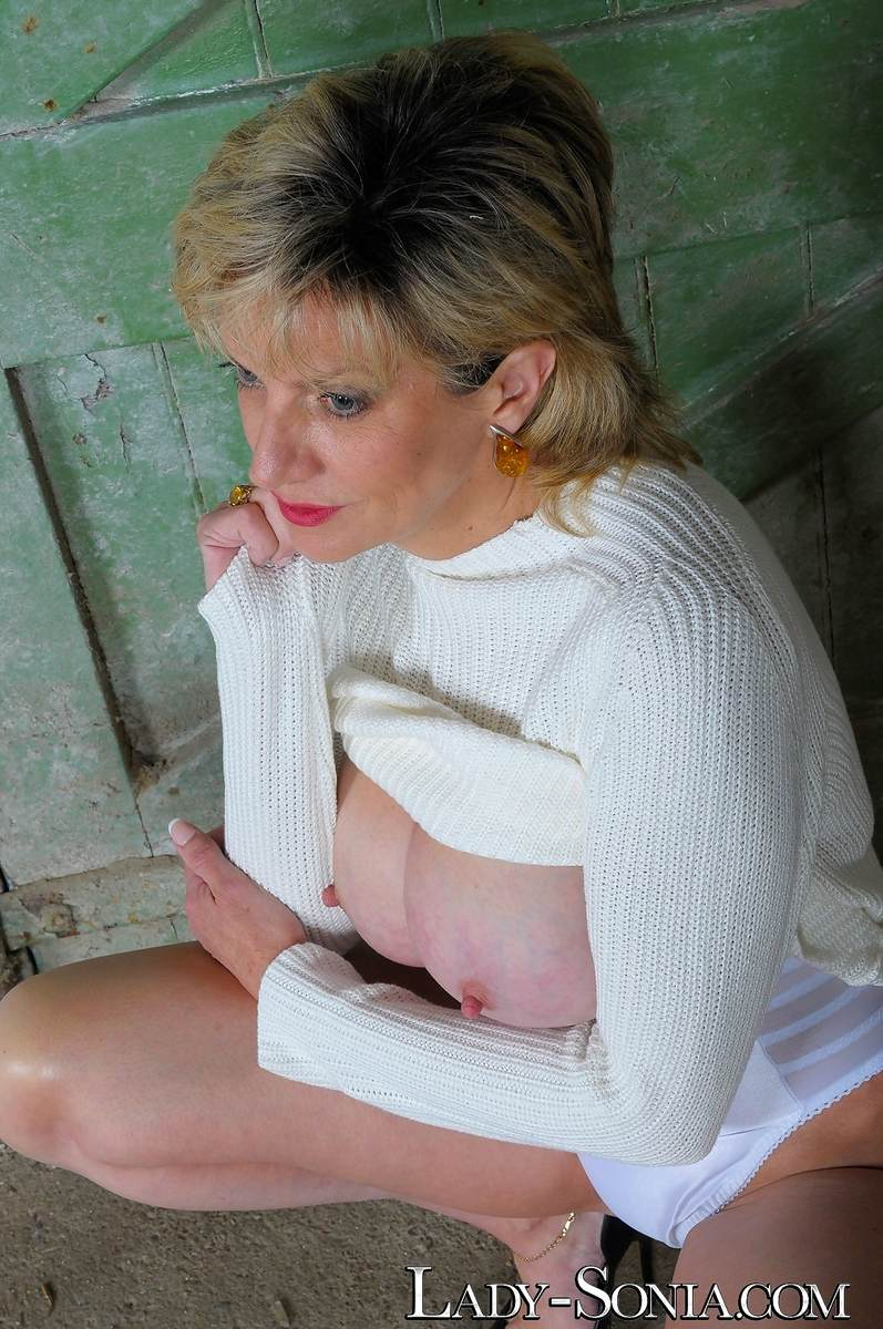 Picture #1 of Mature lady got hot legs and a pair of big boobs to tease men with: wearing heels and panties in this topless scene