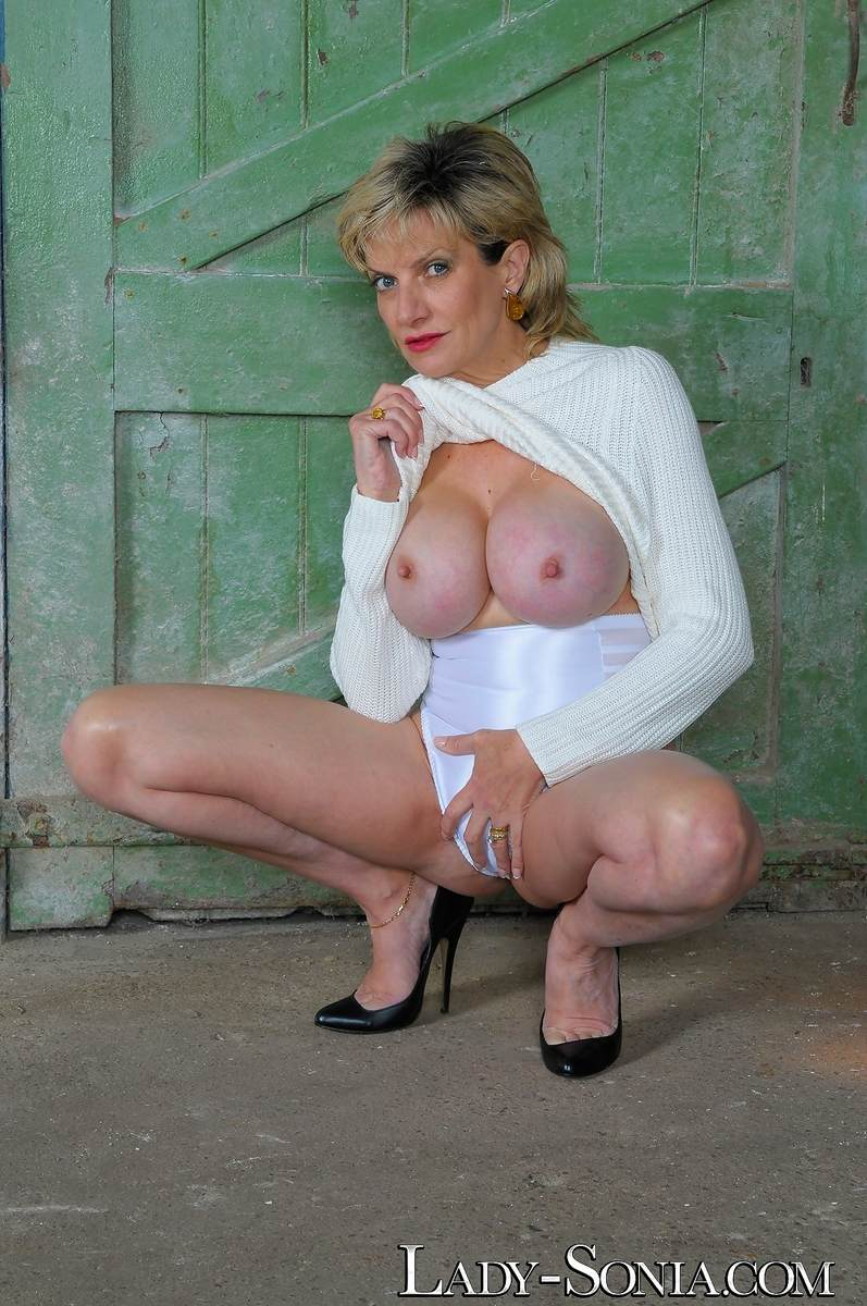 Picture #3 of Mature lady got hot legs and a pair of big boobs to tease men with: wearing heels and panties in this topless scene