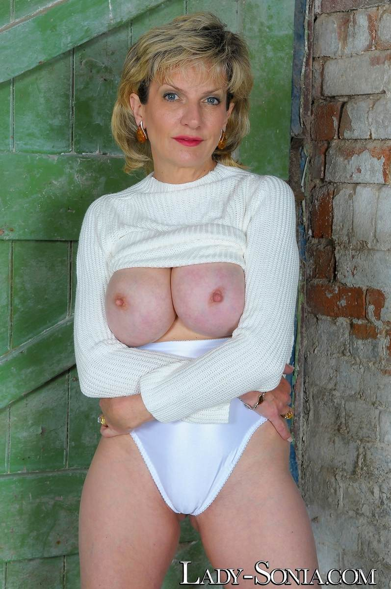 Picture #11 of Mature lady got hot legs and a pair of big boobs to tease men with: wearing heels and panties in this topless scene