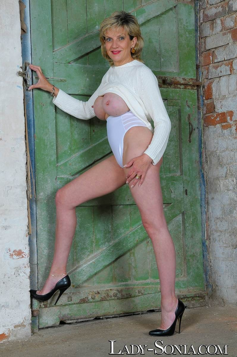 Picture #14 of Mature lady got hot legs and a pair of big boobs to tease men with: wearing heels and panties in this topless scene
