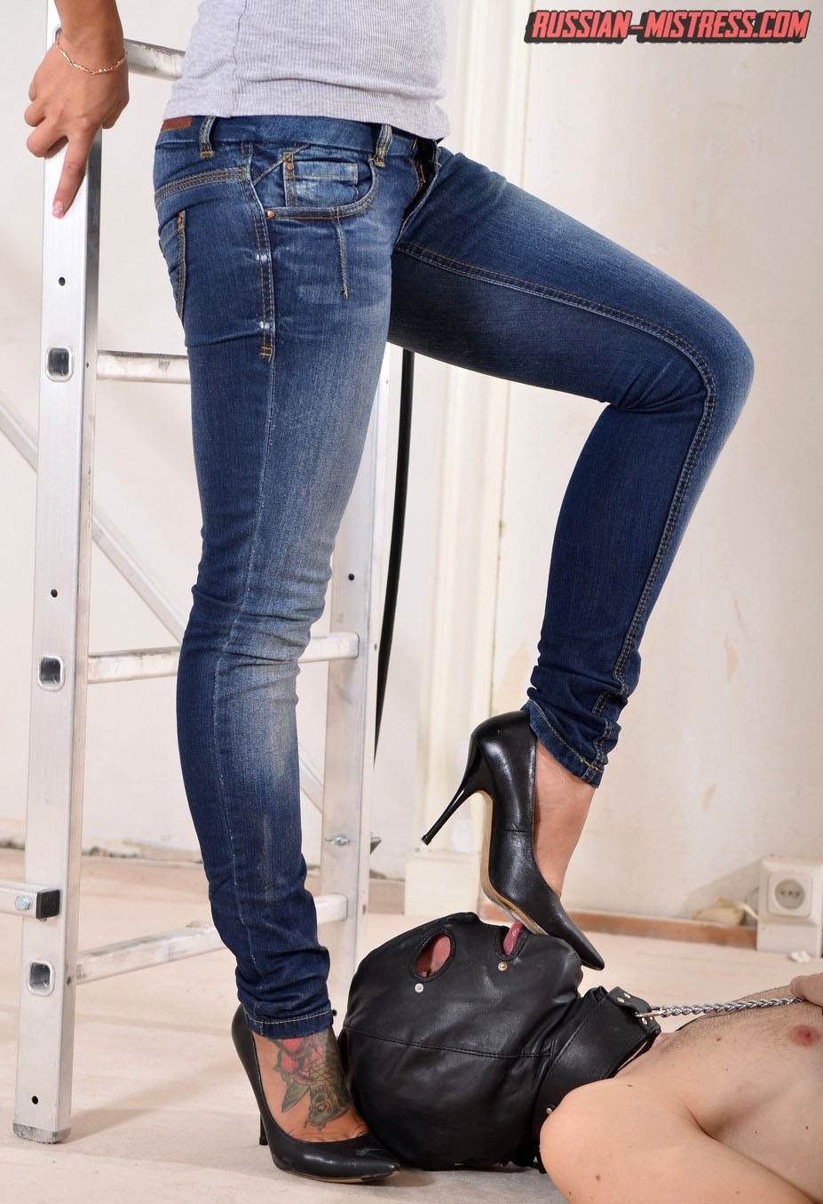 Picture #3 of Babe in sexy jeans and high heels does trampling and then takes out strap-on toy to end femdom lesson with a big bang
