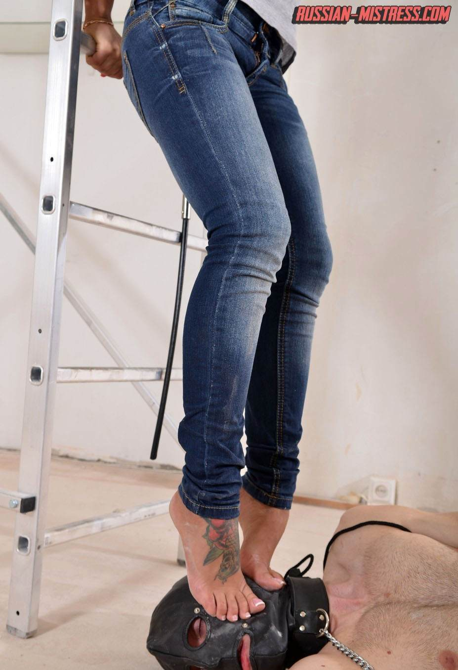 Picture #7 of Babe in sexy jeans and high heels does trampling and then takes out strap-on toy to end femdom lesson with a big bang