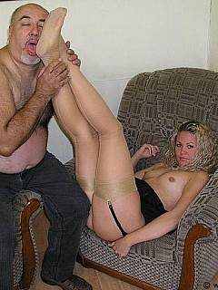 Old pervert is worshiping young blond Goddess making sure her feet in stockings all getting kissed all over