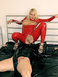 A set of cuffs are used for exposing male slave on top of the bed so slut in red latex could smother and facesit him