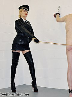 Canning dominatrix is wearing military-style black leather uniform and a pair of knee-boots