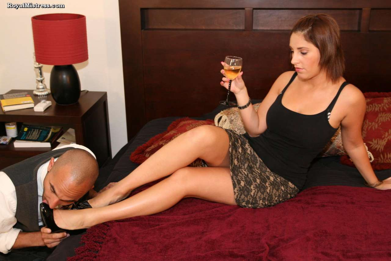 Picture #1 of Leggy babe is enjoying a glass of wine while bald male is worshiping her feet and smelling high heel shoes