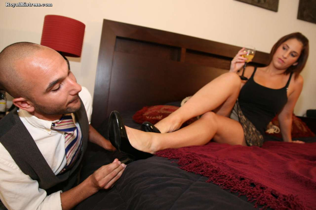 Picture #3 of Leggy babe is enjoying a glass of wine while bald male is worshiping her feet and smelling high heel shoes
