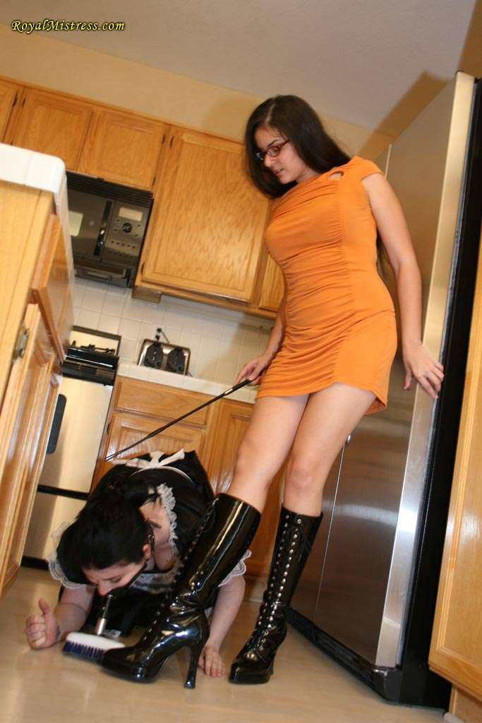 Picture #1 of Maid in submission has two assignments for the day: to clean up the kitchen with brush gag and to lick mistress shiny high heel boots