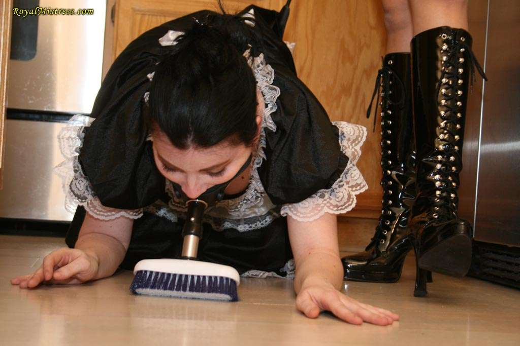 Picture #2 of Maid in submission has two assignments for the day: to clean up the kitchen with brush gag and to lick mistress shiny high heel boots
