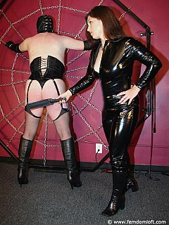 Sissy in garter, heels and nylons is spread-tied and whip-lashed by a couple of hot MILF dommes in black PVC costumes