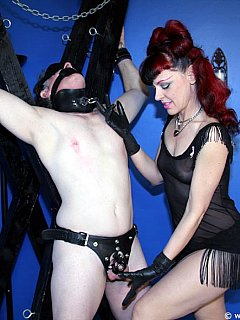 Redhead lady is making use of big gag when tormenting male sub with bizarre CBT and chastity device