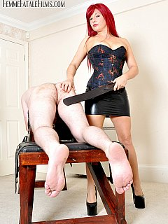 Dude is getting paddled and caned on top of the BDSM rack after classy redhead spitted him in the mouth