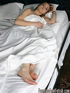 Young mistress undresses and goes naked in bed leaving just her feet outside the blanket for you to desire and worship